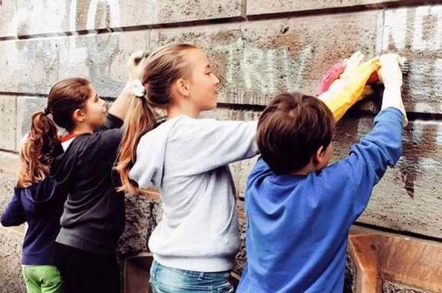 alunni-puliscono-muro